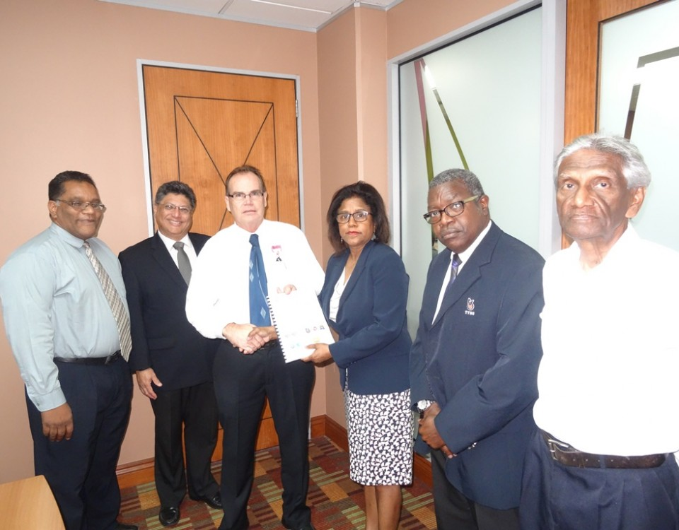 Minister Gopee-Scoon is presented with the project document for the Calidena project by Mr. Robin Phillips, Director of Marketing, Arawak along with officials of PATT and TTBS