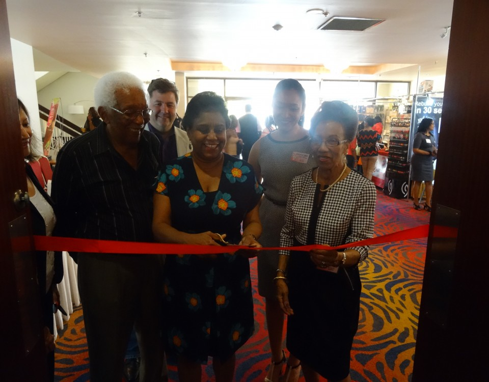 Trade Minister (centre) cuts the ribbon to officially open the trade and beauty show while being flanked by Ms. Monica Headly (right) and Mr. Stokeley Headly (left), Head organisers of the Trade Show