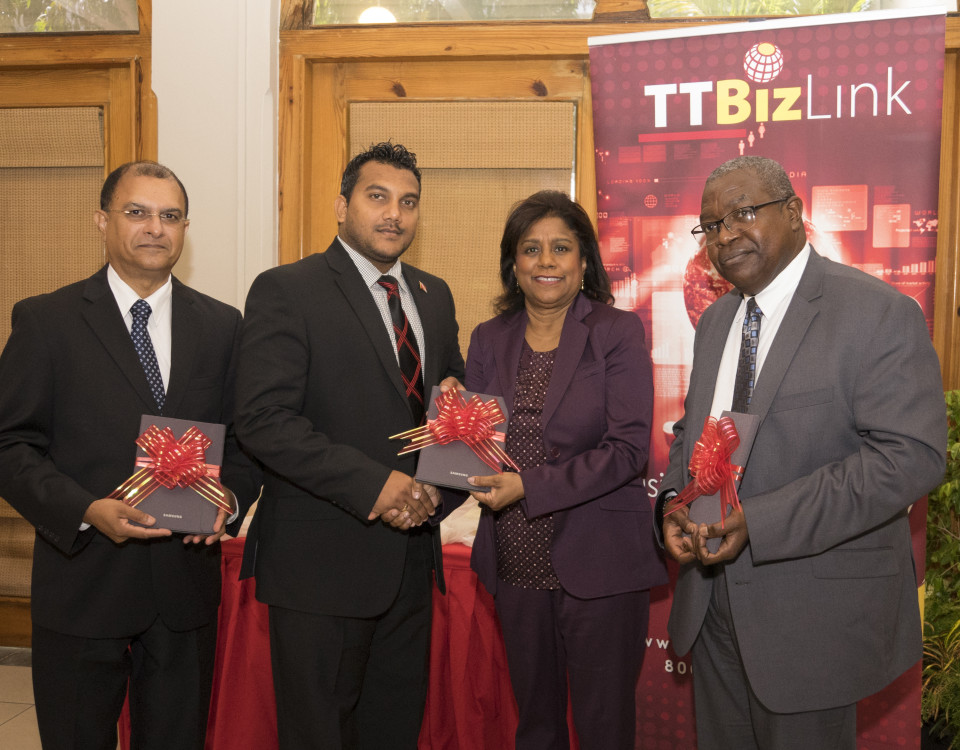 Senator the Honourable Paula Gopee-Scoon, Minister of Trade and Industry presents Senator Avinash Singh with a tablet device along with Dr. Clive Tilluckdharry, Principal Medical Officer, Ministry of Health (left) and Mr. Theodore Reddock, Executive Director (right)
