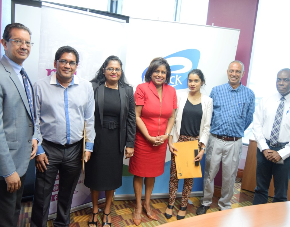 Trade and Industry Minister (centre) flanked by tenants of the Penal/Debe Industrial Park, Mr. Valmiki Ramnarine (2nd right), Ms. Davana Ramnarine (3rd right), Mr. Kelton Pooran (2nd left), Mrs. Jasodra Pooran (3rd left), Mr. Imtiaz Ahamad, Chairman, eTecK Limited (left) and Mr. Ian Fletcher, VP Real Estate Assets (right)