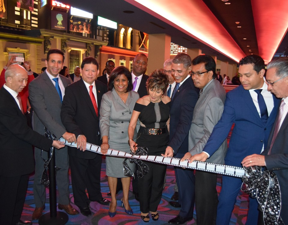 Minister Gopee- Scoon (4th left) looks on as Mrs. Karlene Chin (centre) cuts the ribbon during the formal opening of Movietowne, South