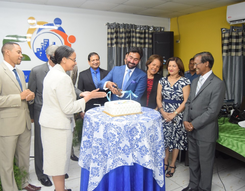 Acting PS Seignoret (left), cuts the ribbon on cake with President Richie Sookai (right) to signify the opening of the Chamber's new office. Looking on are the Executive Directors.