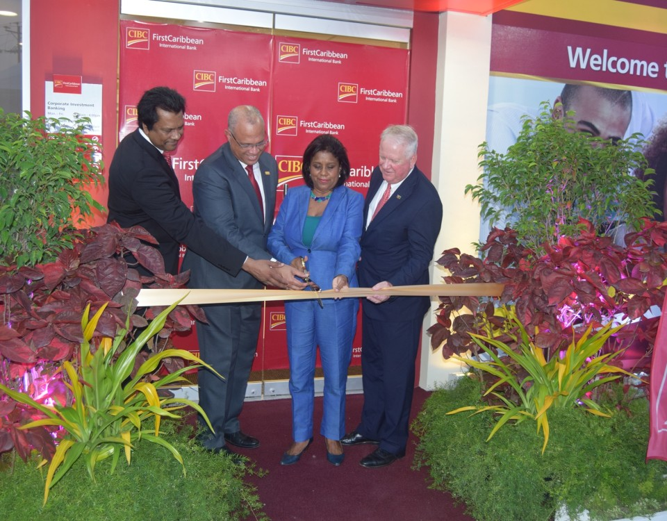 Trade and Industry Minister (centre) cuts the ribbon to officially open the CIBC First Caribbean International Bank, Chaguanas. She is accompanied by Senior Executives of the CIBC.