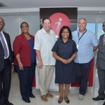 Trade Minister (centre) flanked by Mr. John Swain, Director of Operations, iQor (1-800-Flowers), right and Mr. Brian Henderson, Director of Operations, iQor (Metro PCS), left along with Senior Executives, invest Limited.