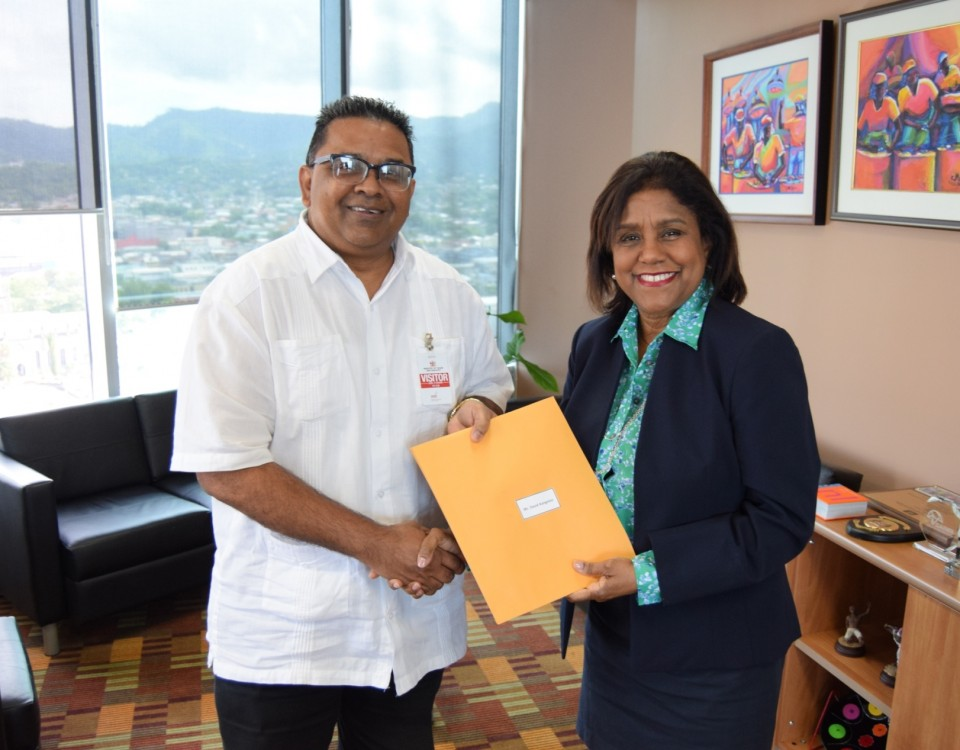 Trade and Industry Minister Paula Gopee-Scoon presents Dr. David Kangaloo, TTRA Chairman with his instrument of appointment