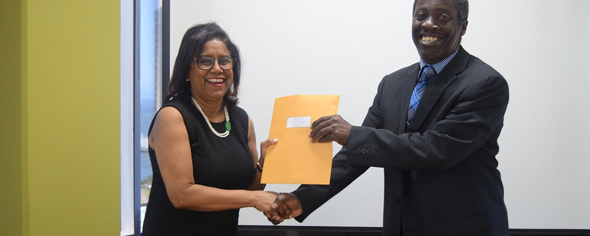 Minister of Trade and Industry Senator the Honourable Paula Gopee-Scoon presents letters of appointment to Mr. Norris Herbert (Co-Chair) of the reconstituted National Trade Facilitation Mr. Norris Herbert (Co-Chair)