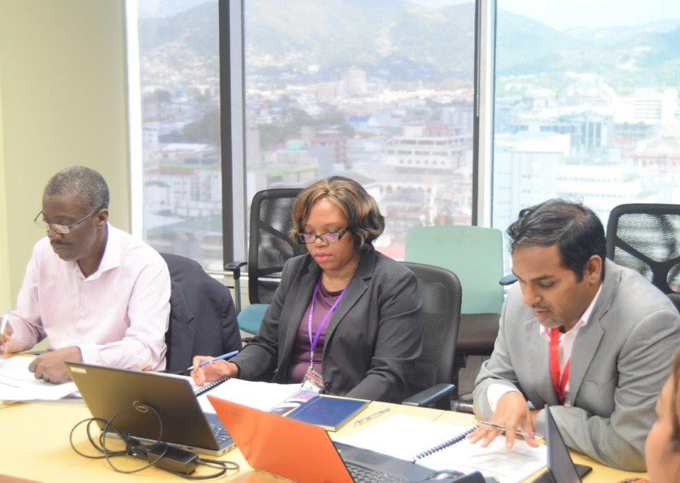 (l-r) Mr Norris Herbert Permanent Secretary Ministry of Trade and Industry reviews documents with MTI senior staff Ms Trudy Lewis and Mr Randall Karim during the Trade Policy Review Consultation