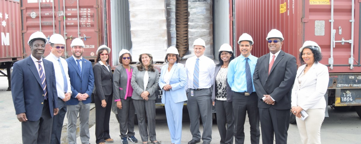 Trade and Industry Minister flanked by Her Excellency, Tania Diego Olite, Cuban Ambassador and Mr. Christian Llanos, Managing Director, Ansa Coatings Ltd and other Executives following the loading of the first shipment of paint to Cuba.
