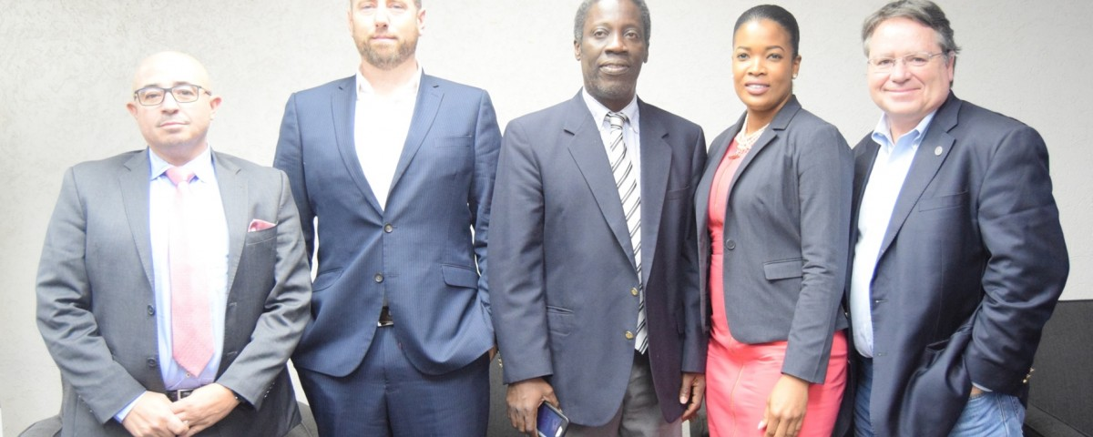 Mr. Norris Herbert, Permanent Secretary, Ministry of Trade and Industry (centre) flanked by presenters of the e-Commerce Forum