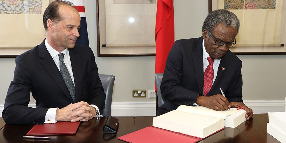 His Excellency Orville London, High Commissioner of the Republic of Trinidad and Tobago to the United Kingdom of Great Britain and Northern Ireland (right) signs CARIFORUM- UK trade agreement as Minister for Trade Policy, George Hollingbery M.P (left), looks on.